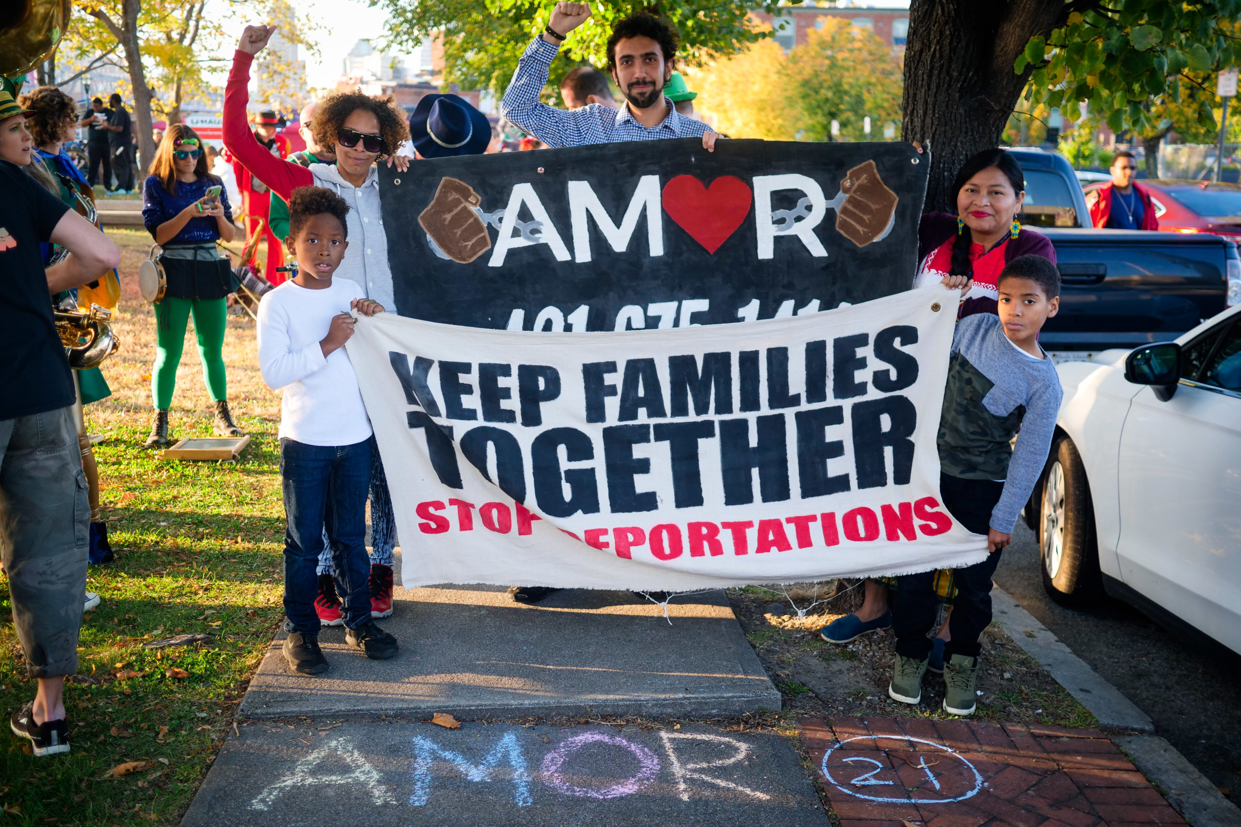 "marching with banner: ""KEEP FAMILIES TOGETHER"""